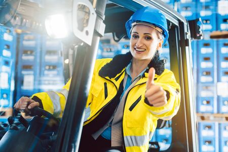 Worker woman showing thumbs up in logistics delivery center sitting in a forklift
