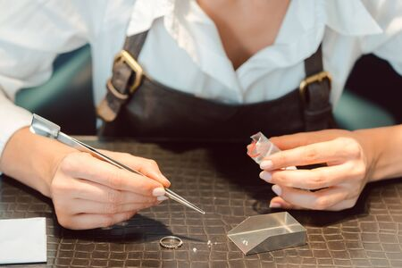 Jeweler sorting diamonds with pincers