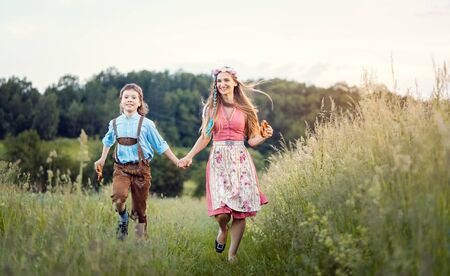 Mother and son in Bavaria running down a path beside a meadow