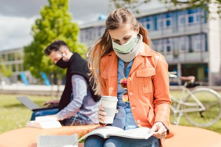 Man and woman practicing social distancing in university while learning and reading