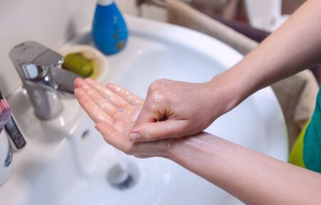 Woman washing her hands thoroughly in bathroom Standard-Bild