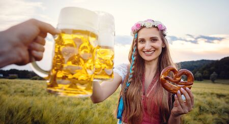 POV shot of couple in Bavaria wearing traditional clothing toasting with beer