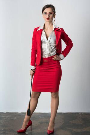 Femme d'affaires en costume rouge avec un fouet prêt à, eh bien, diriger