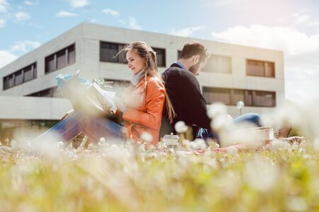 Man and woman student sitting in the grass on university campus reading Standard-Bild