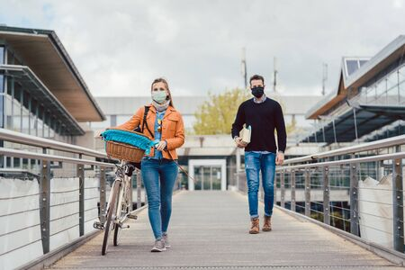 Students on university campus wearing masks during coronavirus crisis keeping social distance
