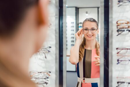 Young woman trying fashionable glasses in optometrist store looking at herself in the mirror Standard-Bild