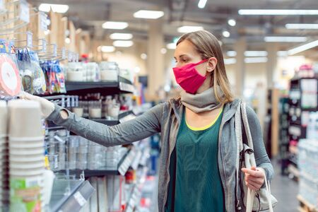 Woman with face mask in supermarket shopping during coronavirus lockdown