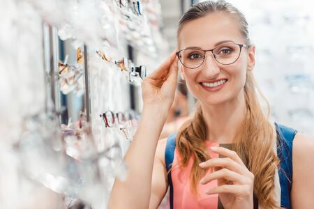Young woman being very happy with her fashionable new glasses looking at the camera