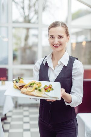 Waitress in a nice restaurant presenting a tasty dish to the camera