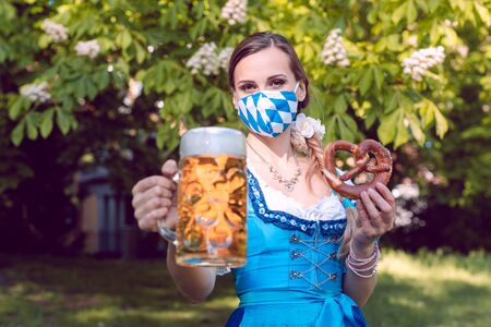 Bavarian woman toasting with beer during covid-19 holding a pretzel