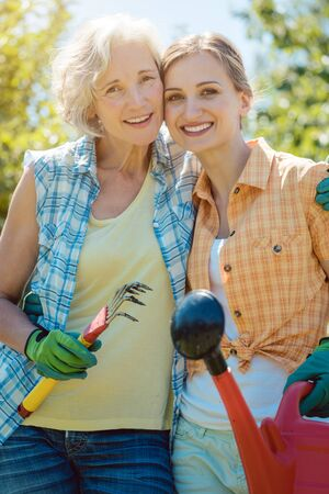Woman gardening together in summer looking at each other