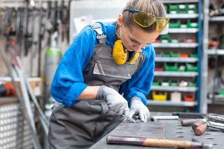 Sideview of worker woman marking piece of metal being absorbed in her work Standard-Bild