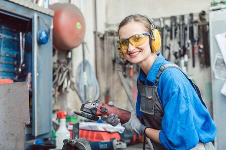 Woman mechanic working with disk grinder on piece of metal