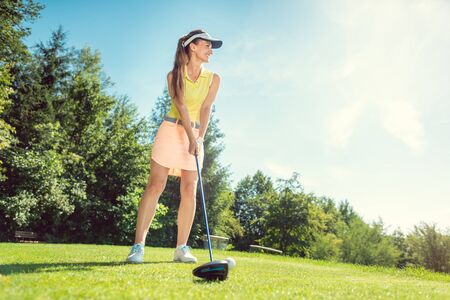 Beautiful woman on golf course at tee, low shot
