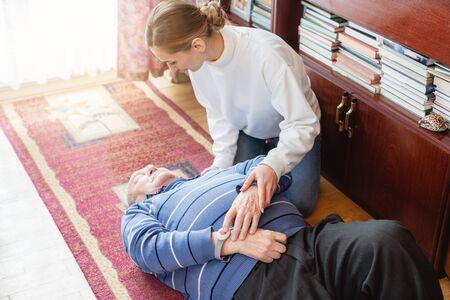 Nurse in assisting living program finding senior man lying on the floor