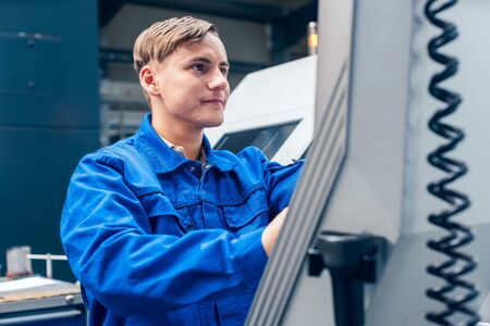 Young male worker programming lathe machine in factory Standard-Bild