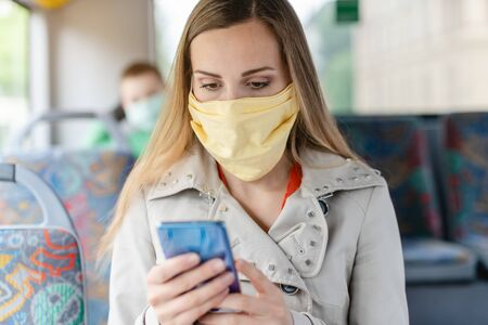 Woman using phone in the bus wearing a face mask because we still have a pandemic