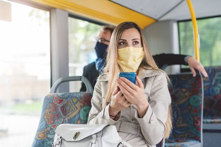People wearing masks in the bus using public transport keeping proper distance Standard-Bild