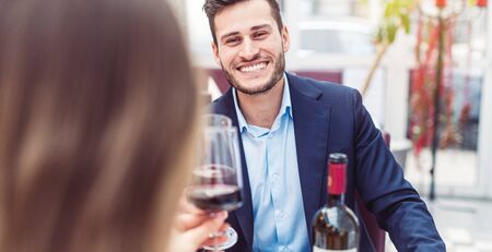 Man and woman enjoying a glass of red wine with their meal having a great time Standard-Bild