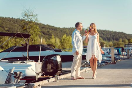 Elegant couple walking between the boats on a river port Standard-Bild