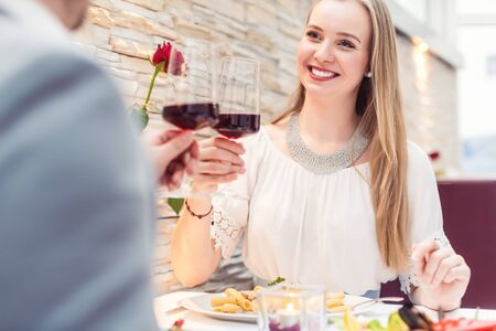 Couple toasting with red wine in romantic restaurant looking at each other