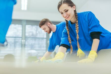 Cleaning crew wiping desks in an office building Zdjęcie Seryjne