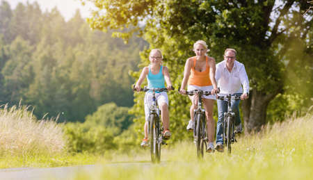 Parents and daughter have bicycle tour on country lane
