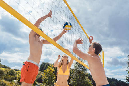 Friends playing beach volleyball hitting ball close at the net Archivio Fotografico - 150759851