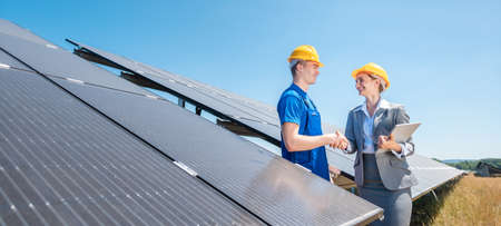 Construction worker and investor in solar power plant shaking hands after completion of the project