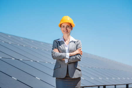 Woman investor in clean energy standing proudly in front of solar panels