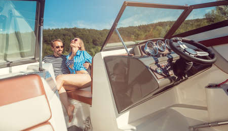 Woman and man enjoying some leisure time on a river boat under a clear blue sky Imagens