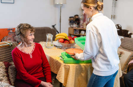 Volunteer serving a meal to senior woman in assisted living program in her kitchen