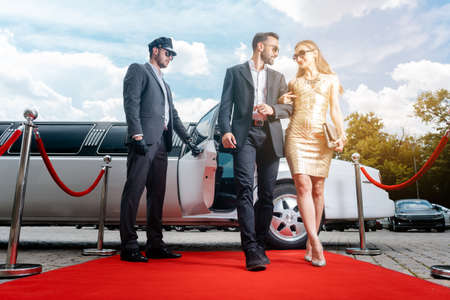 Couple arriving with limousine walking red carpet, a driver is opening the car door