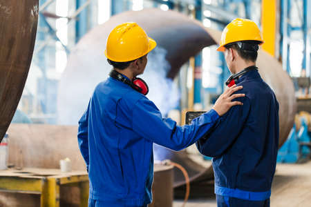 Asian expert checking the quality requirements of manufactured industrial steam boilers