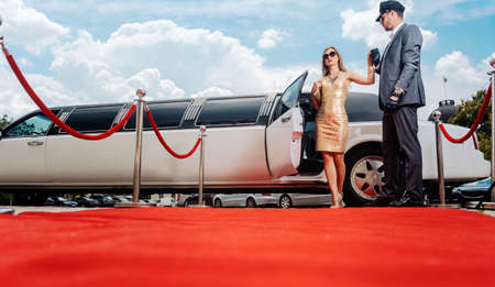 Driver helping VIP woman or star out of limo on red carpet to a reception Standard-Bild