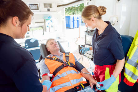 Emergency doctor in ambulance talking to injured man looking cheerful considering the circumstances Foto de archivo