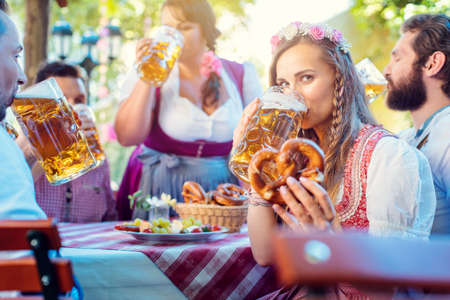 Woman in Tracht looking into camera while drinking a mass of beer surrounded by her friends