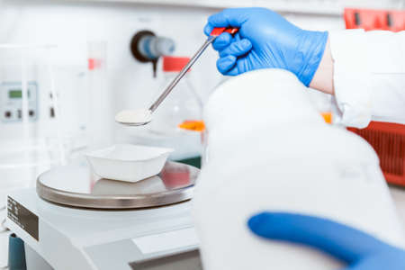 Closeup of pharmacist hand wearing blue gloves pouring white powder chemical on weighing scale in laboratory