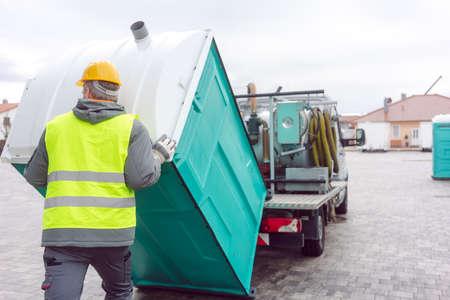 Rental lavatory being loaded on truck by worker Foto de archivo