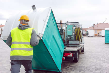 Rental lavatory being loaded on truck by worker Stock Photo
