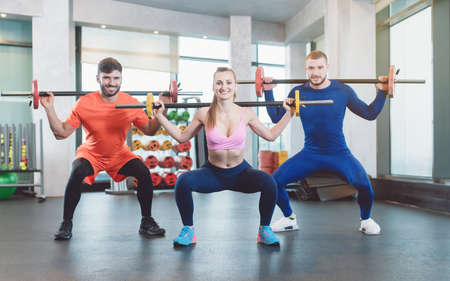 Group of fit young people doing weight exercise in a modern gym