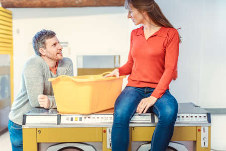 A man chats to a woman sitting on a washing machine in the laundromat 免版税图像
