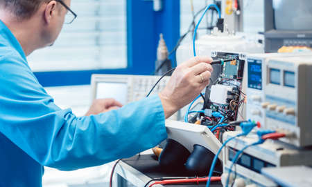 Electronics engineer man troubleshooting defects in a hardware product on his test bench