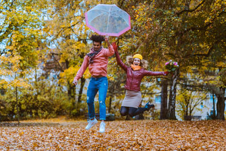 Man and woman jumping joyfully in the autumn park despite the weather