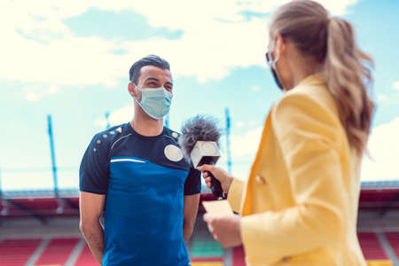Reporter doing interview with football player during covid-19 wearing masks in soccer stadium