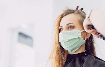 Hairdresser working with stern looking customer waring face mask during pandemic