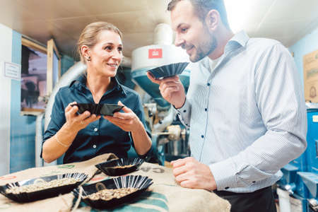 Man and woman with freshly roasted coffee enjoying the aroma