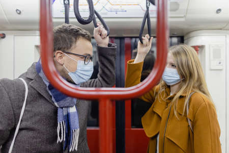 Flirty couple with covid 19 face masks in a train trying to maintain social distance