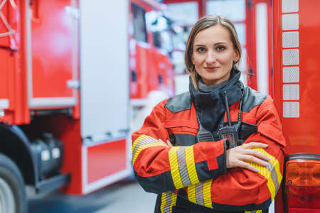 Fire fighter woman standing in front of a fire truck with her arms crossed