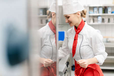 Cook in large commercial kitchen stirring sauce looking at camera
